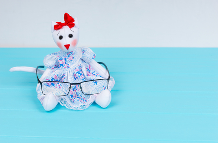Homemade toy in the form of a cat in a dress holding stylish glasses on wooden turquoise board