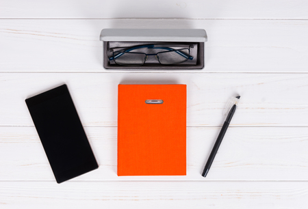 Personal organizer with a pen for making appointments, organising a schedule, glasses in open case for glasses and mobile phone on wooden white table Stock Photo