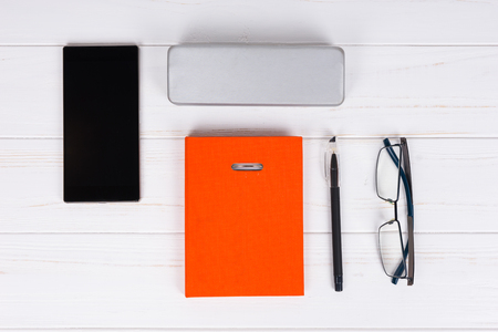 Orange diary with a pen for making appointments, organising a schedule, stylish glasses and a case for glasses near mobile phone on wooden white table Stock Photo