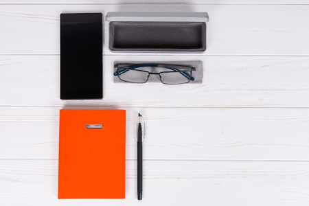 Orange diary with a pen for organising a schedule, glasses and open case for glasses near mobile phone on wooden white table