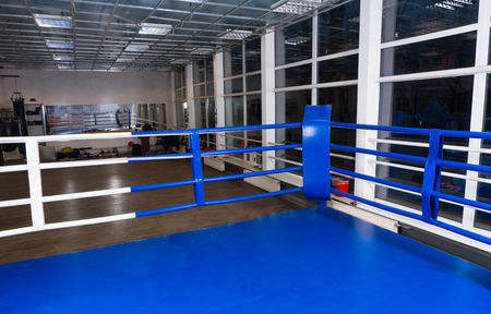 Blue corner of a regular boxing ring surrounded by ropes in a gym with sport equipment