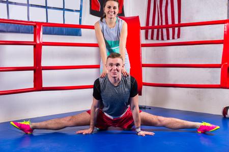 Junger sportlicher Mann, der eine Spalte in der Sportkleidung nahe seiner Freundin im regelmäßigen Boxring in einer Turnhalle tut Standard-Bild - 75709051
