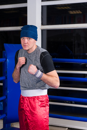 clenching: Athletic boxer standing in a pose clenching his fists in a regular boxing ring surrounded by ropes in a gym Stock Photo