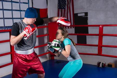 couple on couch: Sporty female doing kickboxing training with her coach in regular boxing ring in a gym