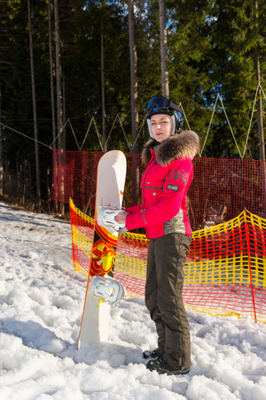 skiers: Beautiful woman in ski suit, helmet and ski goggles standing with snowboard near the fence in a ski-resort in winter period