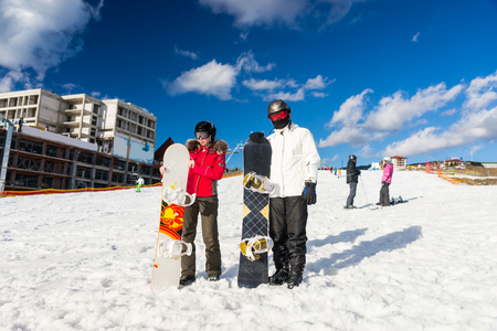 Young couple in ski suits, helmets and ski goggles standing with snowboards in a ski-resort in winter period
