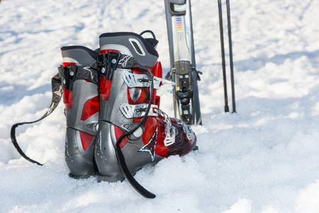 Close up of red and gray boots next to ski laying in fluffy snow in a ski-resort in winter period Imagens