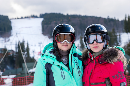Dos mujeres jóvenes en trajes de esquí, con cascos y gafas de esquí de pie en una estación de esquí en período de invierno