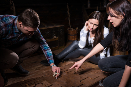 Young people trying to solve a conundrum to get out of the trap, escape the room game concept Foto de archivo