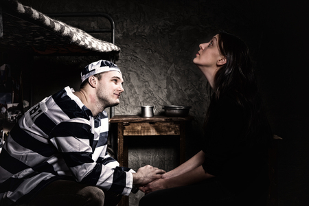 Male prisoner sitting on a bed near bedside table with aluminum dishes and holding female hand, who came to visit him in a small prison cell