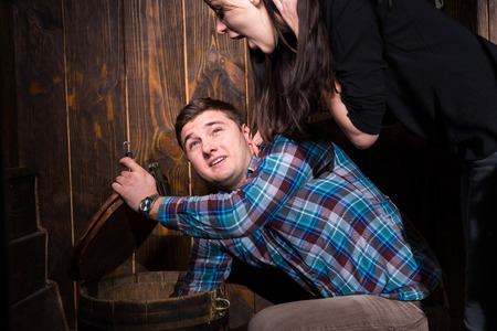 Young male and female opened a barrel and trying to solve a conundrum to get out of the trap, escape the room game concept Reklamní fotografie