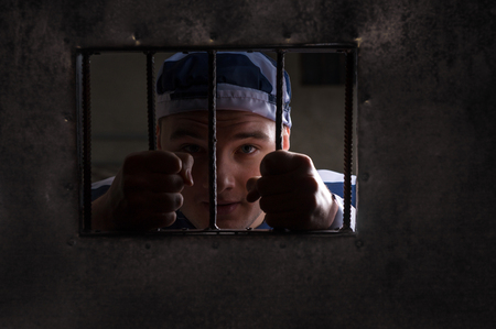 inmate: View through iron door with prison bars on male prisoner holding bars wearing prison uniform in a jail cell