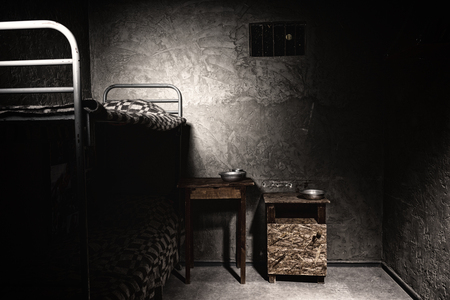 inmate: A dark empty prison cell with bunk bed and bedside table with aluminum dishes