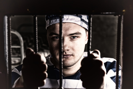 inmate: View through iron door with prison bars on young prisoner holding bars wearing prison uniform in a jail cell