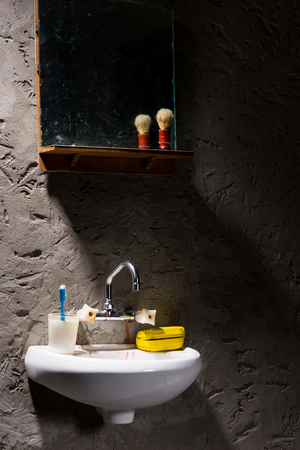 inmate: Washbasin with a glass for a toothbrush and a soap box on it under the mirror with shave brush on the shelf in a prison cell Stock Photo