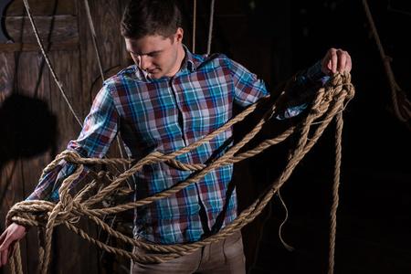 Jeune homme libéré de la captivité et sélectionnant des cordes, échapper au concept de jeu de pièce