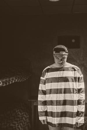 Aggressive male prisoner wearing  prison uniform standing near his bed in a dark prison cell