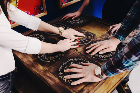 The hands of young people move pieces of the Mexican style trying to get out of the trap, escape the room game concept