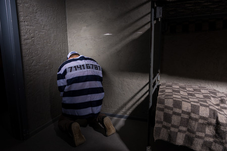 aluminum: Male prisoner wearing  prison uniform with sewed number is sitting in the corner in a small prison cell