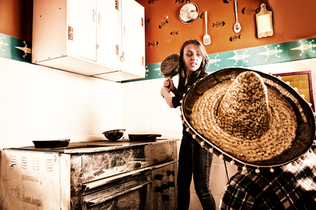 brandishing: Young angry woman brandishing a frying pan at a man in sombrero while standing near old dirty plate with used pans in the kitchen Stock Photo