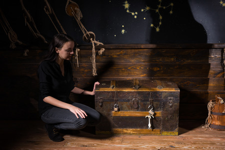 A young girl sits near a chest and trying to find a solution of conundrum to get out of the trap, escape the room game concept Фото со стока
