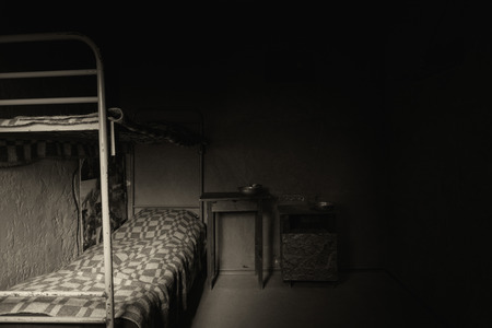 aluminum: Black and white picture of dark empty prison cell with iron bunk bed and bedside table with aluminum dishes Stock Photo