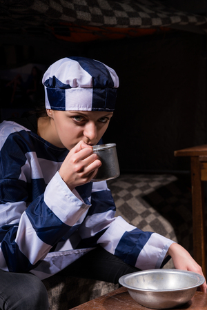 Pensive young female prisoner drinking from an aluminum cup sitting on a bed in a small prison cell