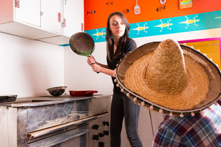 brandishing: Young woman brandishing a frying pan at a man in sombrero while standing near old vintage plate with used pans in the kitchen