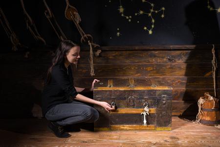 胸トラップから抜け出す、エスケープ部屋ゲームのコンセプトに難問の解決策を見つけるしようとして近くに座っている若い女の子