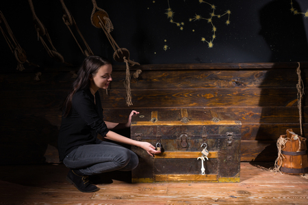 Young girl sits near a chest and trying to find a solution of conundrum to get out of the trap, escape the room game concept