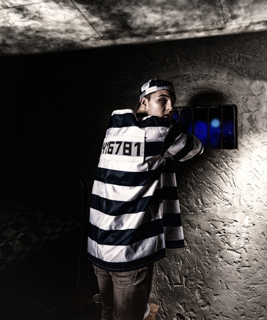 Male prisoner wearing prison uniform looked back while trying to escape through the window with bars in a small dark prison cell
