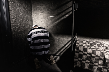 Prisoner wearing  prison uniform with sewed number is sitting in the corner in a small prison cell Фото со стока