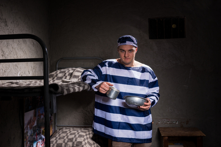 aluminum: Angry male prisoner wearing prison uniform holding aluminum dishes standing near a bunk bed in a prison cell