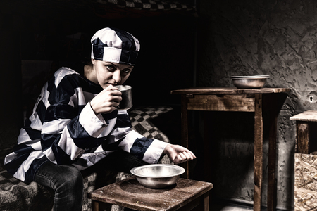 Angry female prisoner wearing prison uniform sitting on a bed and eating from aluminum dishes in a small prison cell Stock Photo