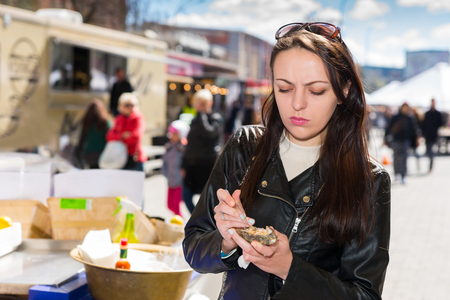 displeased: Displeased woman holding a single fresh opened oyster at outdoor food festival