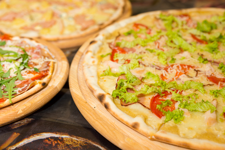 Delicious tasty pizzas with variety of toppings and cheese on wooden trays at outdoor food festival
