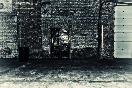 warehouse: Black and white photo of old brick building with a large iron door