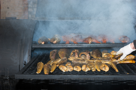 gloved: Gloved hand cooking mixed fried fish on hot grill at food festival