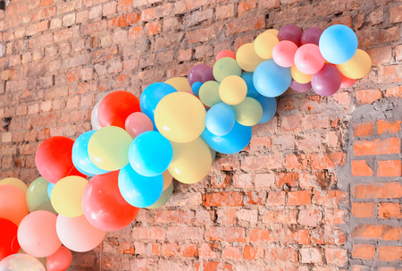 warehouse: Set of multi-colored balls attached to a brick wall