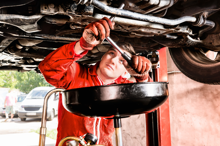 Male mechanic hooking up equipment to the undercarriage of a car elevated on a hoist during repairs and maintenance in a garage workshop
