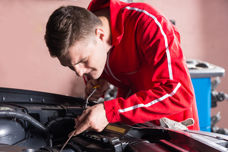 Young mechanic checking the oil level in a car engine holding the dipstick over the open engine compartment