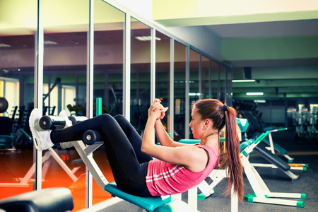 situp: Sporty young woman doing abs training using training apparatus in a gym Stock Photo