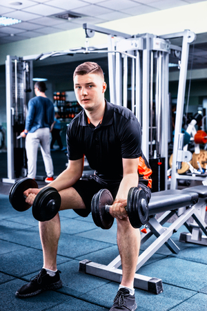 Handsome young sportive man in sportswear lifting some weights and working on his biceps in a gym