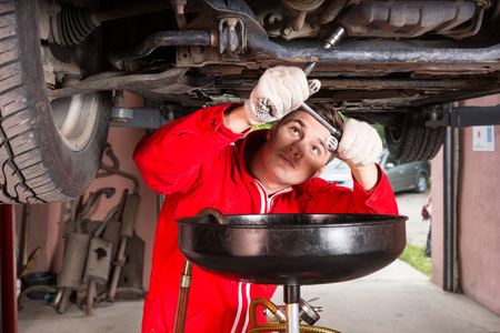 Handsome male car mechanic in uniform working underneath a lifted car and changing motor oil in automobile engine at maintenance repair service station in a car workshop Stock Photo