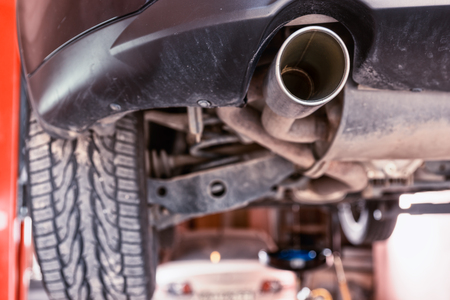 rear end: Close up on the exhaust pipe of a motor car elevated on a hoist in a workshop with focus to the stainless steel tailpiece and opening Stock Photo
