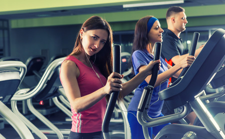 Beautiful woman is looking at the camera while young group of people exercising on the crosstrainer machines in fitness center