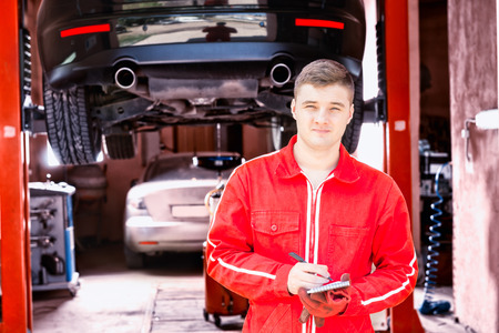 Handsome male motor mechanic standing making notes in front of a black sedan elevated on a hoist in a bay in a garage or workshop