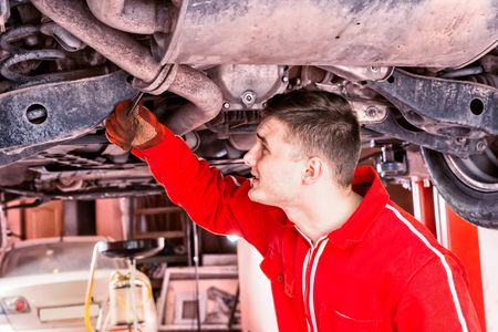 Mechanic in uniform working underneath a lifted car with working equipment for repair and diagnostic in auto repair service