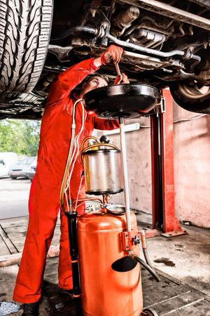 Mechanic hooking up equipment to the undercarriage of a car elevated on a hoist during repairs and maintenance in a garage workshop