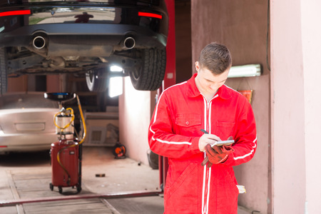 Male motor mechanic standing making notes in front of a black sedan elevated on a hoist in a bay in a garage or workshop Stock Photo